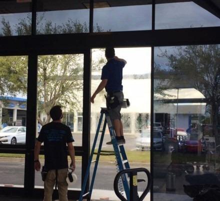 Two men installing window tint