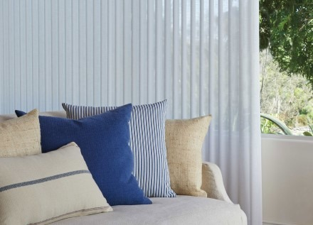 Drapes behind outdoor couch with cushions