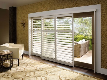 Living room overlooking patio with shutter-covered sliding door