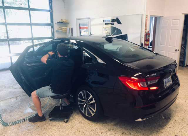 Man installing window tint on a car window